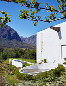 Round rainwater basin and pool in garden against mountain backdrop