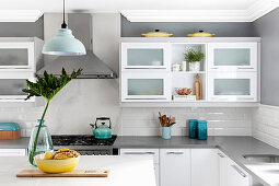 White kitchen counter against pale grey wall with white subway tiles