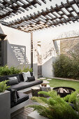 Masonry benches with grey cushions on roofed terrace