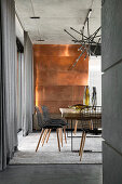 Extravagant dining room in shades of grey with metal-clad wall