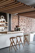 Abstract bar stools at counter in artistic, architect-designed house