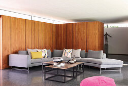 Grey sofa combination against wood panelling in architect-designed house
