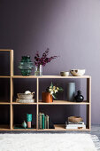 Open wooden shelf with decorative accessories against a violet wall