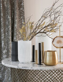 Gold, white and black vases and candle holders on table