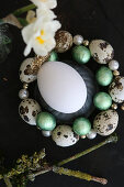 Egg in circlet of threaded quail eggs and beads