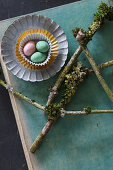 Easter eggs in sweet cases and branches covered with moss and lichen