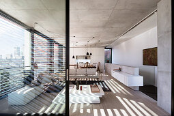 View into open living room with designer furniture, window front and concrete ceiling
