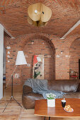 Coffee table, leather sofa and standard lamp in open-plan interior with brick walls