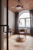 Table, chairs and standard lamp in interior with arched window and brick ceiling