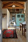 Antiker Esstisch und Klassikerstuhl in umgebauter Scheune, im Hintergrund türkisfarbene Anrichte als Raumteiler