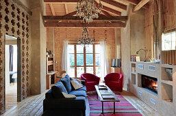 Loungebereich mit Kamin in umgebauter Scheune mit Beton- und Holzwänden