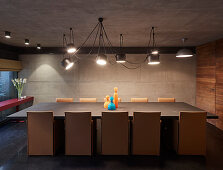 Designer lamp above long dining table in modern architect-designed house