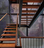 Open-plan, wood and steel staircase with multicoloured stairwell wall