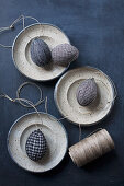 Easter eggs wrapped in fabric and reel of twine