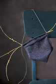 Small hand-sewn bag made from dark fabric on chair backrest