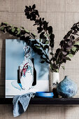 Picture and vase with branches of leaves against wall with designer wallpaper