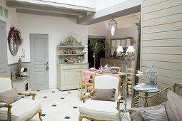 Wohnraum im französischen Stil mit Barocksesseln und Buffetschrank
