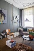 Polstersofa, Coffeetable und Stuhl im Altbau-Wohnzimmer mit dunkler Wand