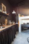 Küchenzeile mit Vorhang und Herd in Küche mit dunkler Wand