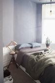 Doppelbett im Schlafzimmer mit grauer Wand