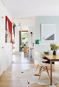 Bright dining room with shell chairs on animal fur rug
