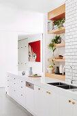White kitchen unit, wooden shelves installed above