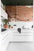 White, L-shaped fitted kitchen with one exposed brick wall