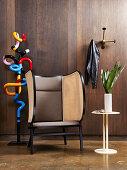 Bunte Skulptur aus Metall, Designer-Ohrensessel und Beistelltisch vor Wand mit dunkler Holzverkleidung