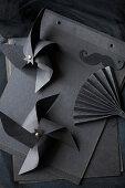 Windräder und ein Fächer aus schwarzem Papier