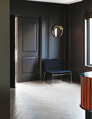 Simple armchair against grey panelled wall