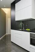 Schlichte weiße Küchenzeile an einer schrägen Wand