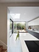 Lange offene Küche mit Fensterfront zum Garten