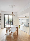White chairs around dining table in front of open doorway leading into open-plan kitchen