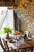 Gedeckter Tisch in alter Scheune mit Natursteinwand