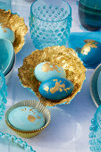 Easter eggs and handmade papier-mâché bowls decorated in blue and gold