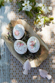 Artistically painted Easter eggs on cress in wooden dish