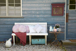 Various cushions with hand-sewn covers on bench outside wooden house