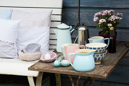 Cushions with hand-sewn covers on bench next to beakers, jugs and Easter eggs on side table