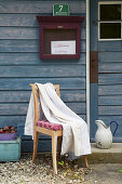 Stuhl mit Bettbezug vor Holzhaus
