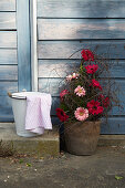 Arrangement of gerbera daisies next to bucket and cloth on stone step