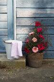 Blumengesteck mit Gerbera neben Steinstufe mit Eimer und Tuch