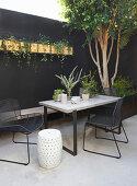Tisch mit Stühlen und Sitzbank vor schwarzer Wand im Innenhof