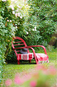 Red rattan lounger in garden