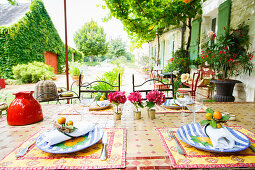 Set table with mosaic top in summery garden