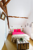 Narrow bedroom with high ceiling and old beams