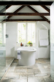 Free-standing bathtub below window in bathroom