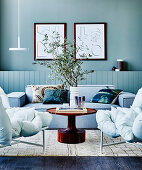 Gray upholstered sofa, round coffee table and split cushion sofa in the living room with gray-green wall