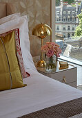 Gilt bedside lamp and vases of roses next to bed