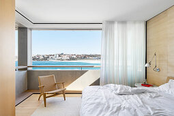 Double bed, wall lamp and designer armchair in front of panoramic window with sea view