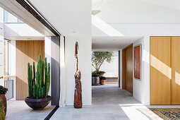 Open living room with tiled floor, cactus shell and sculpture in front of a sliding opening